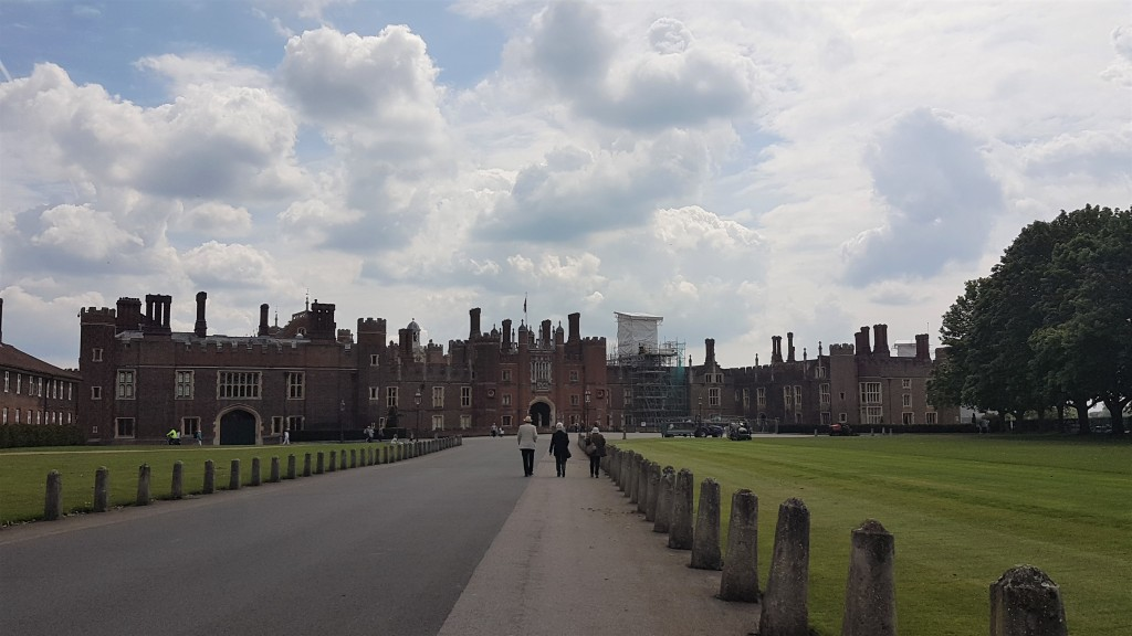 A wide open path leads towards the main entrance to Hampton Court Palace. In the distance, three people walk along the path.